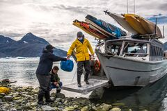 Free Man With Crew Members From Scientific Expedition Unload The Vessel Docked On Iceberg Rock Bay At Wintertime To Explore The Island Stock Photography - 197010992