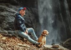 Free Man With Dog Sitting Near Waterfall Stock Photography - 54325662
