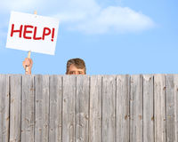 Man With HELP Sign Looking Over Wood Privacy Fence Royalty Free Stock Photos