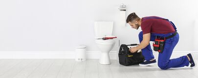 Free Man With Tool Kit Bag Near Toilet Bowl In Bathroom, Space For Text. Banner Design Stock Photo - 185131250