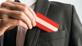 Man withdrawing a wooden card painted as the Austrian flag Royalty Free Stock Photography