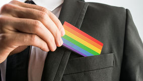 Man withdrawing a wooden card painted as the gay pride flag Royalty Free Stock Photos