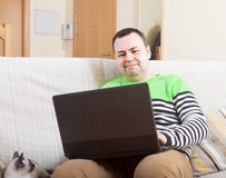 Man withlaptop at home. Adult man sitting at his laptop at home stock photo