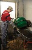 Man woker puts a ready solution in a wheelbarrow Royalty Free Stock Photos