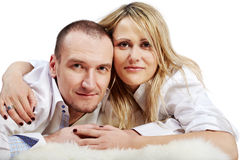 Man and woma lie on white carpet and look Royalty Free Stock Photos