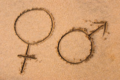 Man and woman. Symbols written on a sandy beach Stock Photography