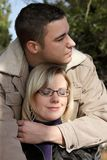 Man and woman. Autumn - outdoor shot of two young people as a couple in love. The man holds the woman with the arm, standing behind her Stock Photography