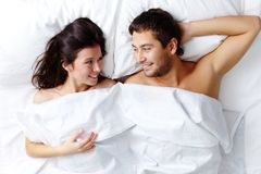 Man and woman. Happy young couple lying in bed and looking at one another Royalty Free Stock Photos
