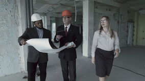 Man, woman, african american in suit and hard hat consider blueprint inside construction site. With colleague. Chief engineer architect with designer show plan stock video footage