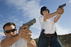 Man And Woman Aiming Hand Guns At Firing Range. Man and women aiming hand guns at firing range during weapons training Stock Image