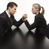 Man and woman arm wrestling. Side view of Caucasian mid-adult businessman and businesswoman arm wrestling on table Royalty Free Stock Photo