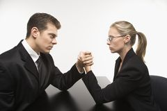 Man and woman arm wrestling. Side view of Caucasian mid-adult businessman and businesswoman arm wrestling on table Stock Photos