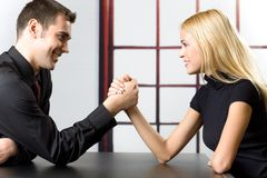 Man and Woman Arm Wrestling. Young happy couple smiling and fighting in arm-wrestling Stock Photography