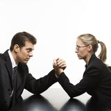 Man and woman arm wrestling on table. Side view of Caucasian mid-adult businessman and businesswoman arm wrestling on table Stock Photography