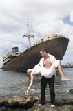 Man with a woman in arms near an abandoned ship Royalty Free Stock Images