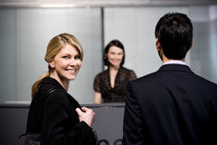 Man and woman arrive at office reception for a business meeting Royalty Free Stock Images