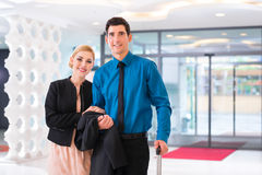 Man and woman arriving at hotel lobby Stock Photos