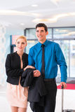 Man and woman arriving at hotel lobby. Man and women arriving at hotel lobby with suitcase Stock Photography