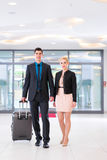 Man and woman arriving at hotel lobby Stock Image