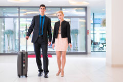 Man and woman arriving at hotel lobby. Man and women arriving at hotel lobby with suitcase Royalty Free Stock Photo