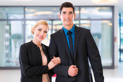 Man and woman arriving at lobby with suitcase Royalty Free Stock Image
