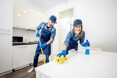 Man and woman as a professional cleaners in the kitchen. Man and women as a professional cleaners in uniform washing floor and wiping furniture in the white stock photos