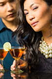 Man and woman in asia at bar with cocktails Royalty Free Stock Photo