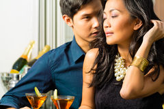Man and woman in asia at bar with cocktails. Asian man and woman in flirting intimately at bar drinking cocktails royalty free stock photography