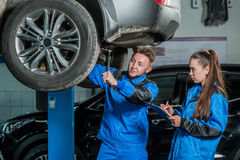 Man and woman in auto mechanics. Man and women auto mechanics in a car workshop at work Royalty Free Stock Photos