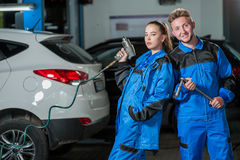 Man and woman in auto mechanics. Man and women auto mechanics in a car workshop at work Stock Photos