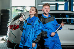 Man and woman in auto mechanics. Man and women auto mechanics in a car workshop at work Royalty Free Stock Image