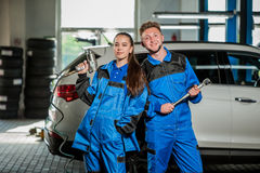 Man and woman in auto mechanics. Man and women auto mechanics in a car workshop at work Stock Photo