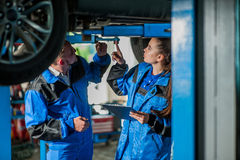 Man and woman in auto mechanics. Man and women auto mechanics in a car workshop at work Royalty Free Stock Photo