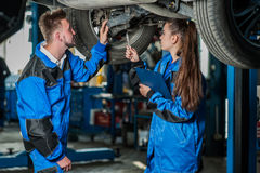 Man and woman in auto mechanics Royalty Free Stock Photo