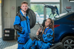 Man and woman in auto mechanics. Man and women auto mechanics in a car workshop at work Stock Photography