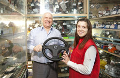 Man and woman  in  auto parts store. Man and women with  steering wheel  in  auto parts store Stock Photo