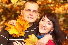 Man and woman with autumn leaves in hands Royalty Free Stock Photo