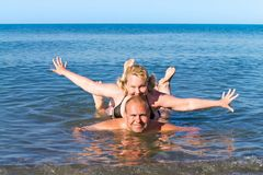 Man and woman of average years play sea as children. Cheerful pair of middle age bathe in the sea Royalty Free Stock Image