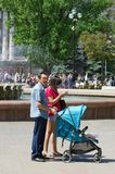 A man and a woman with a baby carriage in a city square near the fountain royalty free stock photos