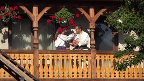 Man, woman and baby with traditional clothes at wooden house balcony, parents kissing child, family portrait