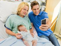 Man With Woman And Babygirl Taking Selfportrait. Mid adult men with women and newborn babygirl taking selfportrait through mobile phone in hospital room Stock Photo