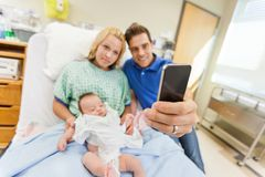 Man With Woman And Babygirl Taking Selfportrait. Man with women and newborn babygirl taking selfportrait through cell phone in hospital room Stock Image