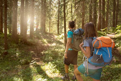 Man and woman with backpack walking on hiking trail path in forest woods during sunny day.Group of friends people summer. Man and women with backpack walking on Stock Photos