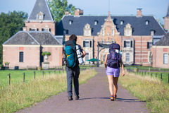 Man and woman with backpacks walking to castle Royalty Free Stock Images