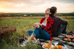 Man and woman with backs to each other on sunset. Man and women sitting with their backs to each other on sunset, picnic in the field. Romantic junket on sunset royalty free stock image