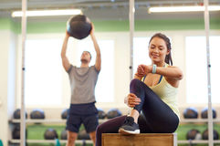 Man and woman with ball and fitness tracker in gym. Sport, training and people concept - men exercising with medicine ball and women tracking time on fitness stock images