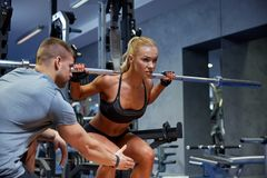 Man and woman with bar flexing muscles in gym stock photos