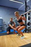 Man and woman with bar flexing muscles in gym Royalty Free Stock Photos