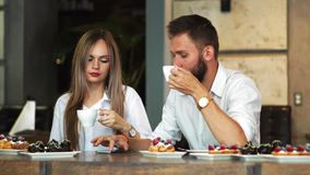 Man and woman at the bar having a coffee and using a mobile phone.  stock footage
