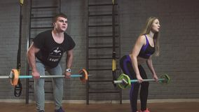Man and woman with barbell flexing muscles in gym. Slow motion stock video footage